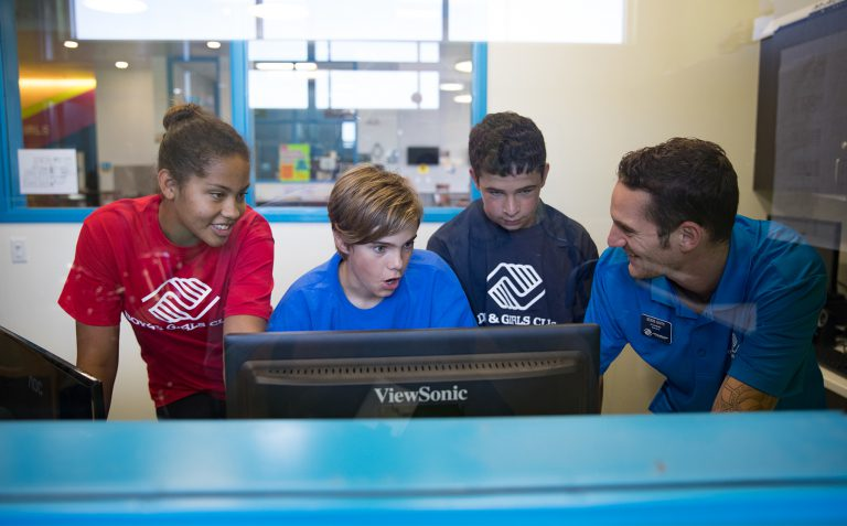 Mentor using a computer with students